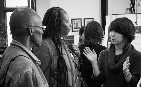 Patricia Price, principal of PS/MS 161 in Harlem (second from the left), learns about the CCNY student presentations from Katherine Cho, service-learning coordinator.