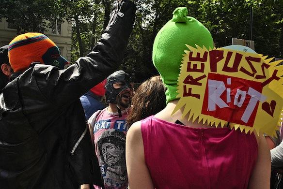 Protestors in balaclavas (as worn by members of Pussy Riot) protest Pussy Riot members' arrest.
